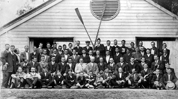Group photo of the Club's founding members in front of the original boat-shed.